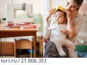 Купить «Мама с младенцем сидит у стола со швейной машинкой», фото № 21806351, снято 26 января 2016 г. (c) Евгений Майнагашев / Фотобанк Лори