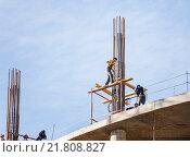 Купить «Арматурщики вяжут арматуру колонны высотного здания», эксклюзивное фото № 21808827, снято 6 октября 2013 г. (c) Владимир Чинин / Фотобанк Лори
