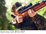 Купить «soldier or hunter shooting with gun in forest», фото № 21813107, снято 14 августа 2014 г. (c) Syda Productions / Фотобанк Лори