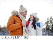 Купить «happy couple with tea cups over winter landscape», фото № 21814163, снято 23 января 2016 г. (c) Syda Productions / Фотобанк Лори