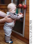 Маленький мальчик держит в руках красный шар на гирлянде. Стоковое фото, фотограф Наталья Чумакова / Фотобанк Лори