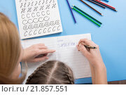 Купить «Мама помогает ребенку правильно писать буквы алфавита, вид сверху», фото № 21857551, снято 20 января 2016 г. (c) Иванов Алексей / Фотобанк Лори