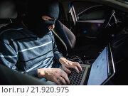 Купить «Преступник в маске работает на ноутбуке и сидит в автомобиле», фото № 21920975, снято 19 февраля 2016 г. (c) Mark Agnor / Фотобанк Лори