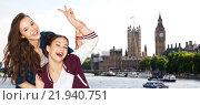 Купить «happy teenage girls showing peace sign in london», фото № 21940751, снято 19 декабря 2015 г. (c) Syda Productions / Фотобанк Лори
