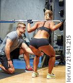 Купить «man and woman with barbell flexing muscles in gym», фото № 21941215, снято 19 апреля 2015 г. (c) Syda Productions / Фотобанк Лори