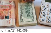 Две пачки денег, Российские рубли и американские доллары лежат рядом и калькулятор. Стоковое видео, видеограф Яна Королёва / Фотобанк Лори