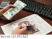 Купить «Кассир пересчитывает заработную плату на фоне трудового договора», эксклюзивное фото № 21971827, снято 25 февраля 2016 г. (c) Игорь Низов / Фотобанк Лори
