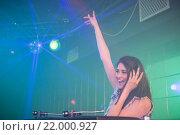 Купить «Pretty female DJ waving her hand while playing music», фото № 22000927, снято 22 сентября 2015 г. (c) Wavebreak Media / Фотобанк Лори