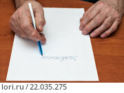 Купить «Пенсионер пишет заявление на листе бумаги за столом», эксклюзивное фото № 22035275, снято 3 марта 2016 г. (c) Игорь Низов / Фотобанк Лори