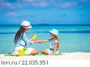 Купить «Молодая мама наносит солнцезащитный крем на руки маленькой девочки», фото № 22035951, снято 4 апреля 2015 г. (c) Дмитрий Травников / Фотобанк Лори
