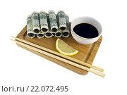 Купить «Свернутые доллары, ломтик лимона, соевый соус в белой чашке и палочки на доске», фото № 22072495, снято 5 января 2015 г. (c) Анна Жидкова / Фотобанк Лори