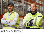 Купить «smiling men in reflective uniform at warehouse», фото № 22079691, снято 9 декабря 2015 г. (c) Syda Productions / Фотобанк Лори
