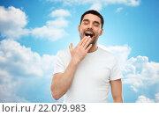 Купить «yawning man over blue sky background», фото № 22079983, снято 15 января 2016 г. (c) Syda Productions / Фотобанк Лори