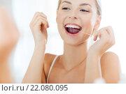 Купить «woman with dental floss cleaning teeth at bathroom», фото № 22080095, снято 13 февраля 2016 г. (c) Syda Productions / Фотобанк Лори