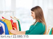 Купить «happy woman choosing clothes at home wardrobe», фото № 22080115, снято 19 февраля 2016 г. (c) Syda Productions / Фотобанк Лори