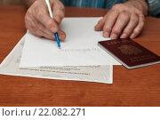 Купить «Взрослый мужчина пишет заявление на листке бумаги на фоне свидетельства о праве на наследство», эксклюзивное фото № 22082271, снято 3 марта 2016 г. (c) Игорь Низов / Фотобанк Лори