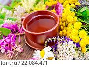Tea from wild flowers in clay cup on board. Стоковое фото, фотограф Zoonar/kostrez / easy Fotostock / Фотобанк Лори