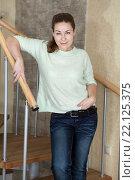 Портрет довольной женщины в джинсах, стоящей на винтовой лестнице. Стоковое фото, фотограф Кекяляйнен Андрей / Фотобанк Лори