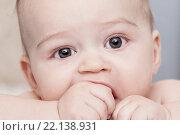 Ребенок кусается свой кулак и смотрит в камеру. Стоковое фото, фотограф Ирина Столярова / Фотобанк Лори