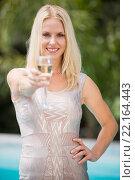 Portrait of happy woman offering champagne flute. Стоковое фото, агентство Wavebreak Media / Фотобанк Лори