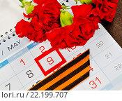 Купить «Георгиевская лента и красные гвоздики на календаре с датой 9 мая», фото № 22199707, снято 13 марта 2016 г. (c) Зезелина Марина / Фотобанк Лори