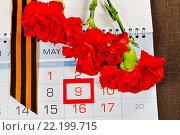 Купить «Георгиевская лента и красные гвоздики на календаре с датой 9 мая», фото № 22199715, снято 13 марта 2016 г. (c) Зезелина Марина / Фотобанк Лори