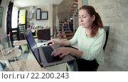 Купить «Девушка сидит на кухне за стеклянным столом и работает на ноутбуке, вид сбоку, широкий угол», видеоролик № 22200243, снято 15 марта 2016 г. (c) Кекяляйнен Андрей / Фотобанк Лори