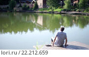 Купить «Young man on the lake», видеоролик № 22212659, снято 14 марта 2016 г. (c) Raev Denis / Фотобанк Лори
