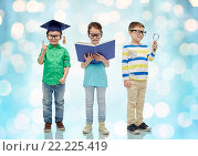 Купить «kids in glasses with book, lense and bachelor hat», фото № 22225419, снято 31 января 2016 г. (c) Syda Productions / Фотобанк Лори
