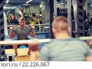 Купить «young man flexing muscles with barbell in gym», фото № 22226067, снято 19 апреля 2015 г. (c) Syda Productions / Фотобанк Лори