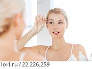 Купить «woman with tweezers tweezing eyebrow at bathroom», фото № 22226259, снято 13 февраля 2016 г. (c) Syda Productions / Фотобанк Лори