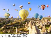 Купить «Hot air balloon flying over rock landscape at Cappadocia, Turkey», фото № 22227407, снято 19 мая 2015 г. (c) Наталья Волкова / Фотобанк Лори