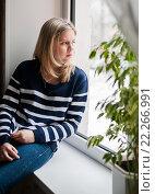 Купить «Грустная девушка сидит на подоконнике и смотрит в окно», эксклюзивное фото № 22266991, снято 8 марта 2016 г. (c) Игорь Низов / Фотобанк Лори