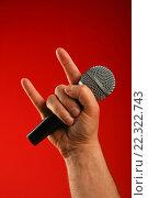 Купить «Рука с микрофоном показывает козу на красном фоне», фото № 22322743, снято 4 февраля 2016 г. (c) Anton Eine / Фотобанк Лори