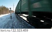Купить «Товарный состав с вагонами проносится мимо по зимней железной дороге, крупный план», видеоролик № 22323459, снято 21 марта 2016 г. (c) Кекяляйнен Андрей / Фотобанк Лори