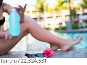 Женщина держит солнцезащитный крем, сидя около бассейна. Стоковое фото, фотограф Дмитрий Травников / Фотобанк Лори
