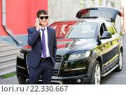 Купить «Молодой предприниматель в костюме и очках говорит по телефону рядом с дорогим автомобилем», фото № 22330667, снято 25 июля 2015 г. (c) Евгений Майнагашев / Фотобанк Лори