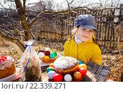 Купить «Девочка в кепке и куртке сидит за столом на природе. На столе пасхальные блюда», фото № 22339271, снято 19 марта 2011 г. (c) Анна Кирьякова / Фотобанк Лори