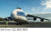 Купить «Человек (авиатехник из обслуживающего персонала аэропорта), идущий перед самолетом Ан-124-100 Руслан (крупнейший в мире российский грузовой самолет), в аэропорту Порт-Морсби, Папуа-Новая-Гвинея, в солнечный летний день на фоне облачного неба», фото № 22363963, снято 2 июля 2020 г. (c) oleg savichev / Фотобанк Лори