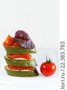 Крупный план бутербродов с красной рыбой, базиликом и томатами черри на светлом фоне. Стоковое фото, фотограф Козлова Анастасия / Фотобанк Лори