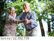 Happy senior woman dancing with husband against trees. Стоковое фото, агентство Wavebreak Media / Фотобанк Лори