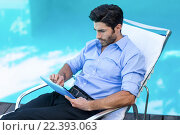 Купить «Smart man using digital tablet near pool», фото № 22393063, снято 28 ноября 2015 г. (c) Wavebreak Media / Фотобанк Лори