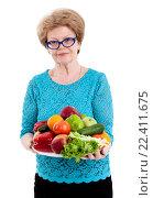 Купить «Пожилая счастливая женщина держит поднос с фруктами и овощами в руках, изолировано белом фоне», фото № 22411675, снято 26 марта 2016 г. (c) Кекяляйнен Андрей / Фотобанк Лори