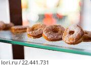 Купить «close up of sugared donuts on showcase shelf», фото № 22441731, снято 15 февраля 2016 г. (c) Syda Productions / Фотобанк Лори