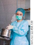 Купить «Портрет медицинской сестры в процедурном кабинете держит в руках стерилизационный бикс и смотрит в камеру», фото № 22458139, снято 27 марта 2016 г. (c) Эдуард Паравян / Фотобанк Лори