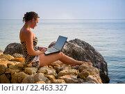 Купить «Девушка сидит на камнях у моря с ноутбуком на коленях», фото № 22463327, снято 9 июля 2015 г. (c) Александр Никифоров / Фотобанк Лори