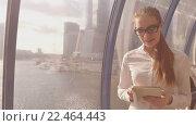 Купить «Молодая красивая деловая женщина с планшетом в руках на фоне офисных зданий», видеоролик № 22464443, снято 4 апреля 2016 г. (c) Серёга / Фотобанк Лори