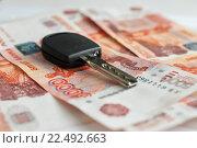 Купить «Покупка автомобиля. Автомобильные ключи лежат на фоне из российских денег. Крупный план», эксклюзивное фото № 22492663, снято 4 апреля 2016 г. (c) Игорь Низов / Фотобанк Лори
