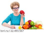 Купить «Пожилая женщина смотрит на красный сладкий перец в руке, сидит возле фруктов и овощей, изолировано на белом фоне», фото № 22493567, снято 26 марта 2016 г. (c) Кекяляйнен Андрей / Фотобанк Лори