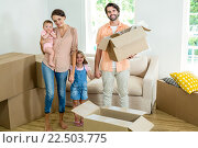 Купить «Happy family standing with boxes in new house», фото № 22503775, снято 18 декабря 2015 г. (c) Wavebreak Media / Фотобанк Лори